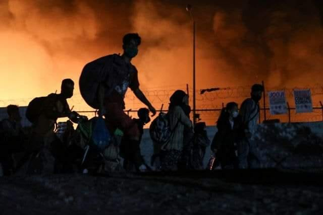 A picture of a group of people fleeing the Moria refugee camp on Lesvos, Greece while it is burning on 8 September 2020